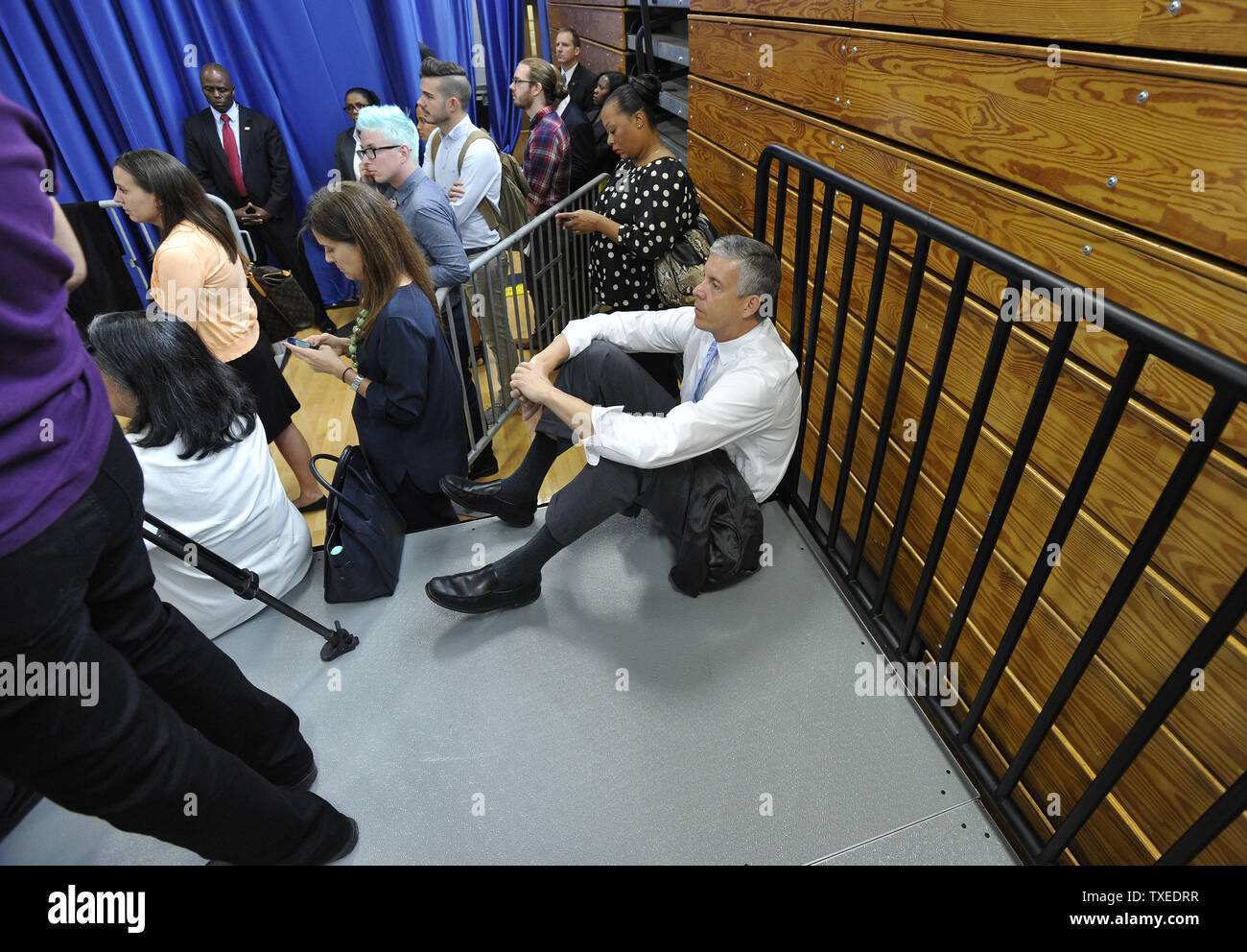 Education Secretary Arne Duncan takes off his jacket and sits on a press riser as he listens to First Lady Michelle Obama as they bring education initiatives to Booker T. Washington high school during a Reach Higher rally with students on September 8, in Atlanta. UPI/David Tulis - Stock Image