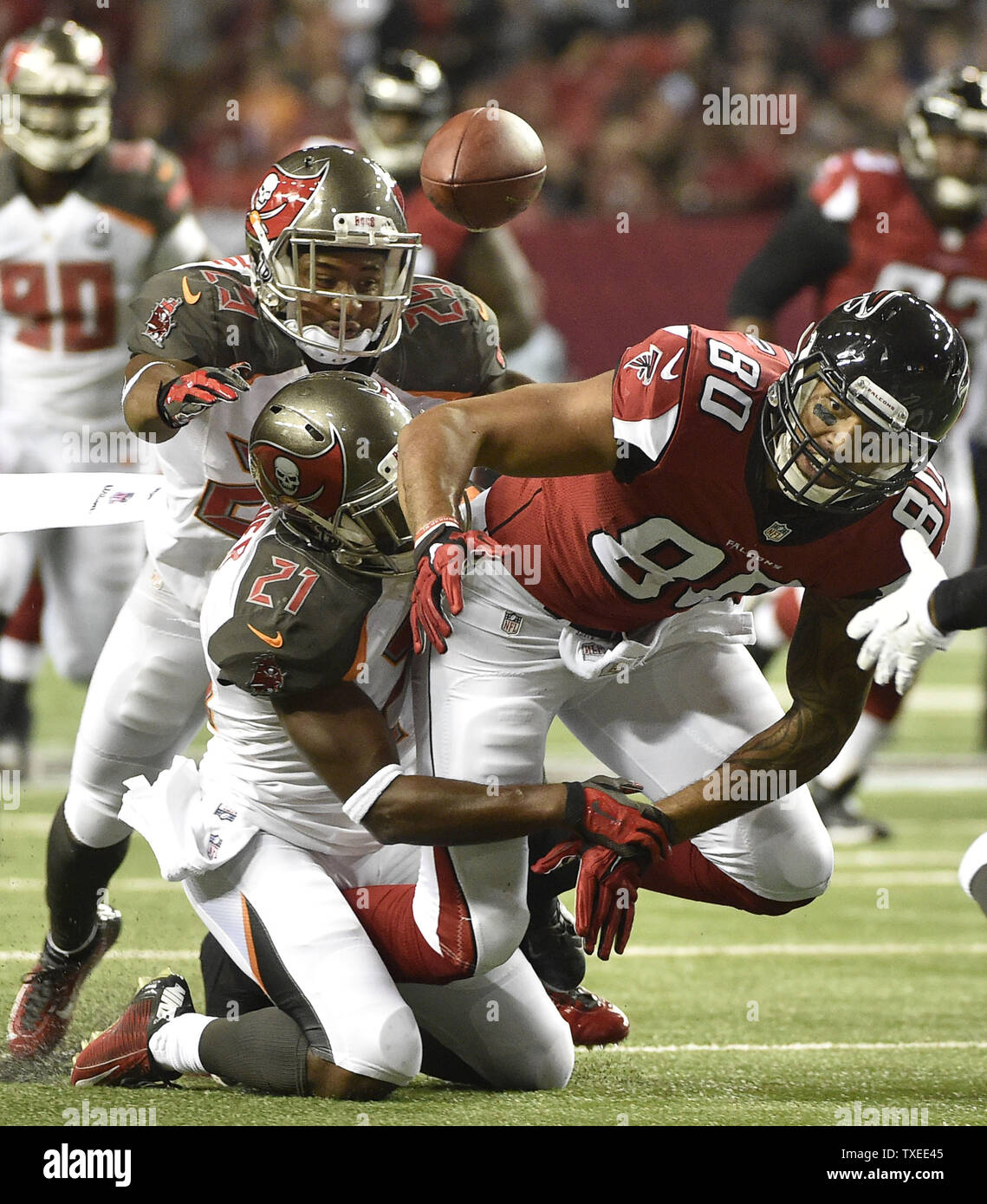 Atlanta Falcons tight end Levine Toilolo (80) fumbles the ball away under pressure from Tampa Bay Buccaneers cornerbacks Alterraun Verner (21) and Leonard Johnson (29) during the first half of their football game at the Georgia Dome in Atlanta on September 18, 2014. Tampa recovered briefly but Atlanta regained possession when Tampa fumbled before the play was over. UPI/David Tulis Stock Photo