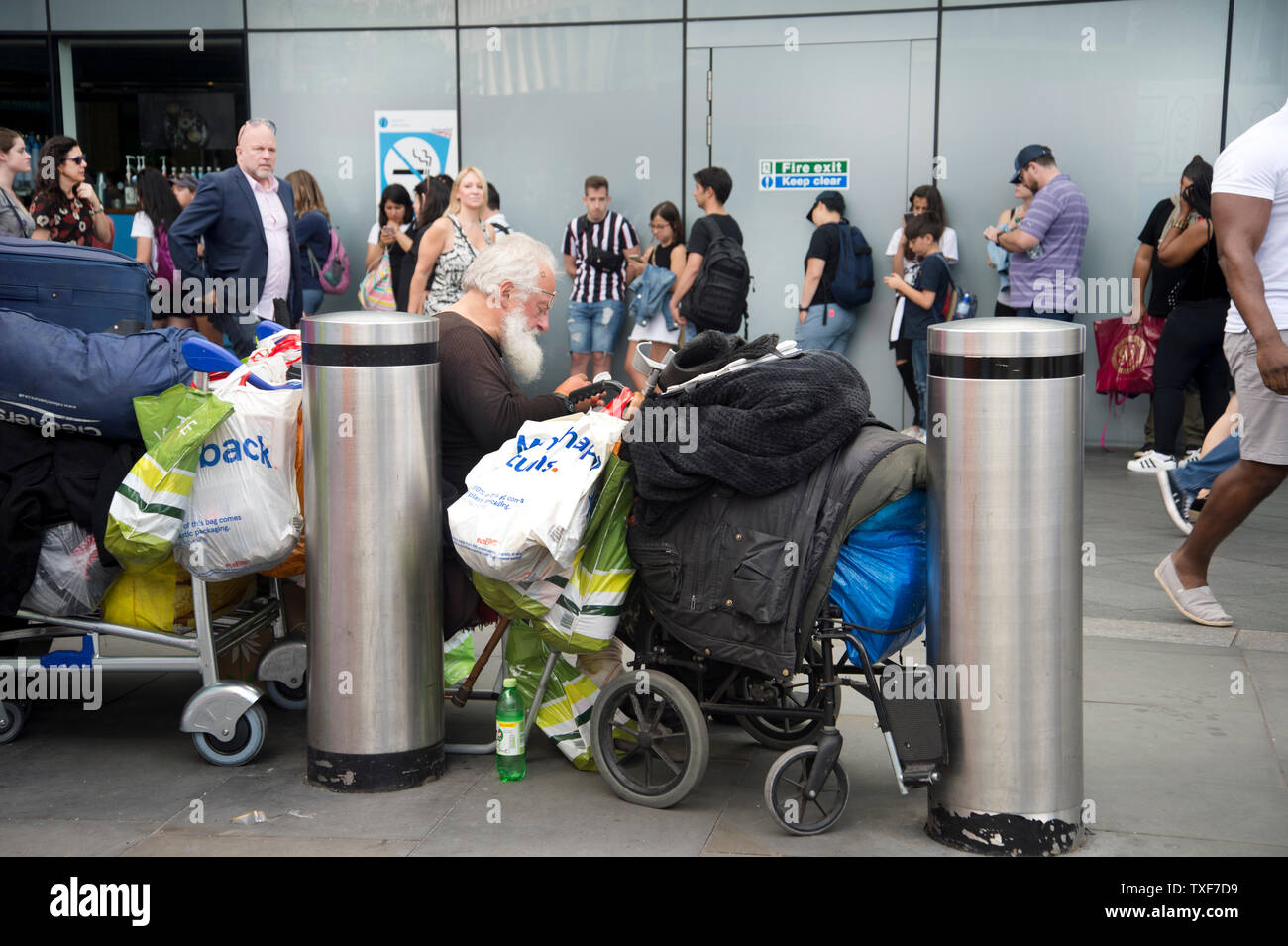 London, Kings Cross. A homeless elderly man with his possessions on trolleys in front of the queue of Harry Potter fans. - Stock Image