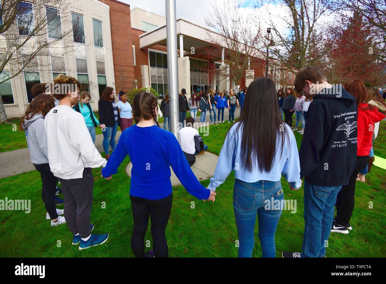 Grants Pass High School students participate in a prayer circle during a national walkout to honor Florida school shooting victims, in Grants Pass, Oregon, March 14, 2018. The youth-organized protest brought attention to school safety, protested gun violence, and honored the 17 victims of the shooting at Marjory Stoneman Douglas High School. Photo by David Tulis/UPI Stock Photo
