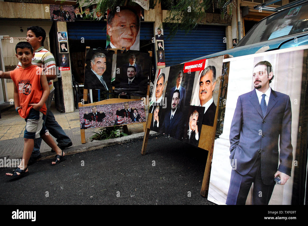 Lebanese kids walk past campaign posters for Saad Hariri, son of the popular slain ex PM Rafik Hariri, in Beirut the evening before parliamentary elections are due to take place on May 28, 2005. The elections will be the first in thirty years to be held without the presence of Syrian troops in Lebanon.  It is typical of Lebanese politics that a relative of a popular leader should ride the wave of popularity into public office. (UPI Photo/Stewart Innes) Stock Photo