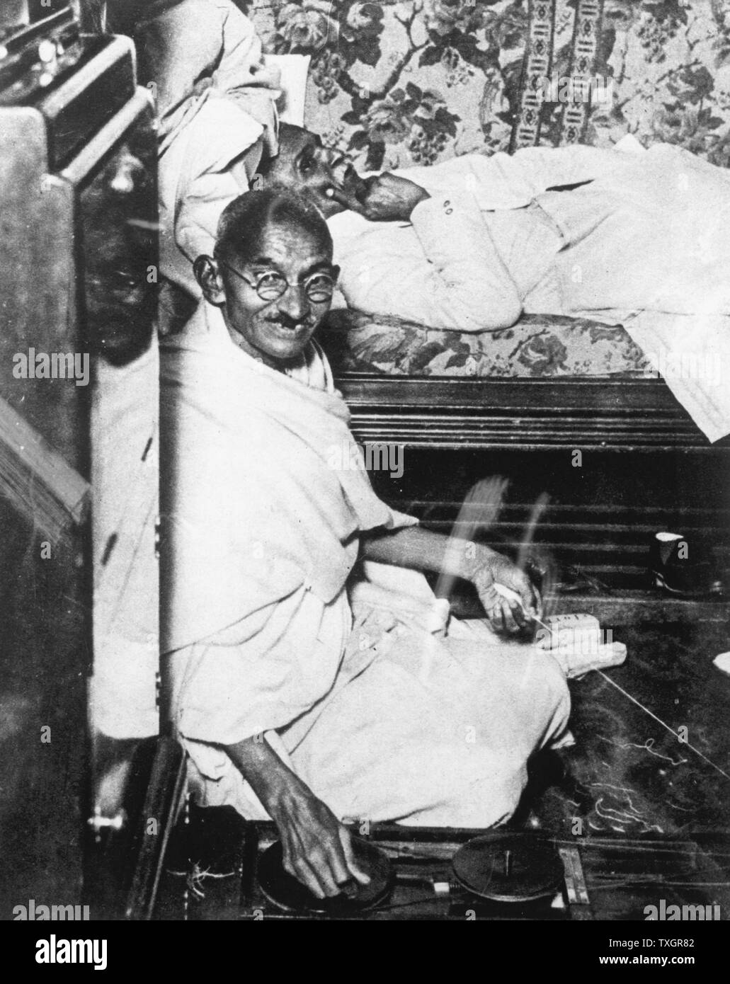 Mohondas Karamchand Gandhi  (1869-1948), known as Mahatma (Great Soul), Indian Nationalist leader. Here he is working at his spinning wheel, a symbolic task he performed almost daily. - Stock Image