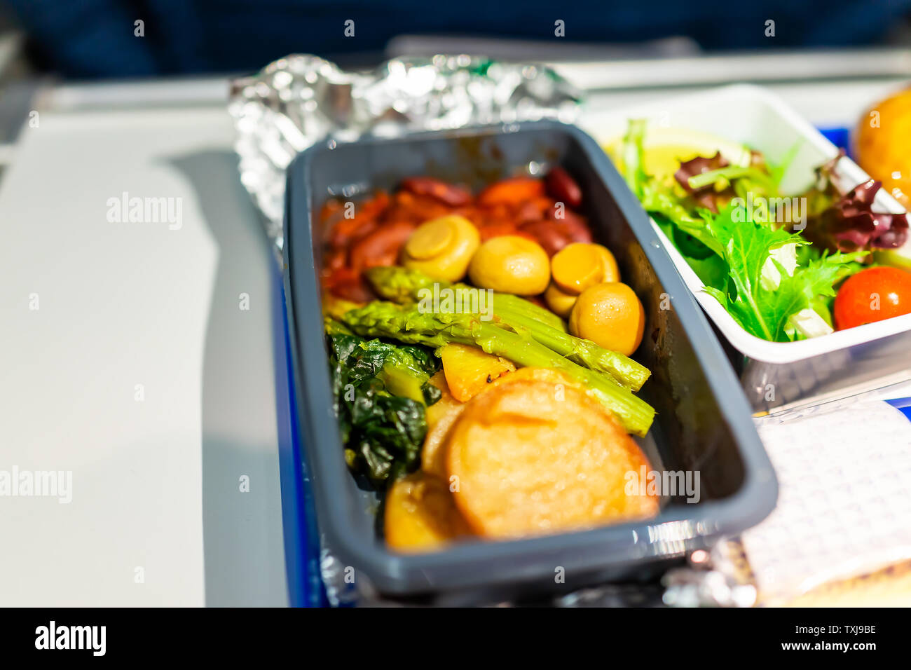 Healthy vegan vegetarian food hot vgml meal macro closeup on airplane flight with potato mushrooms asparagus vegetables on tray with salad - Stock Image