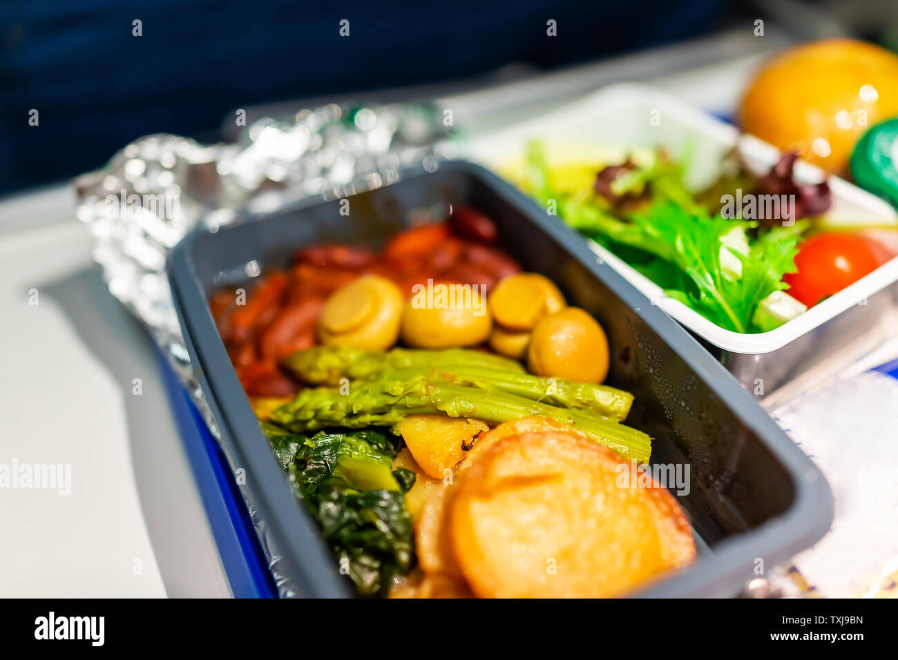 Healthy vegan vegetarian food hot vgml meal on airplane flight with potato mushrooms asparagus vegetables on tray with salad - Stock Image