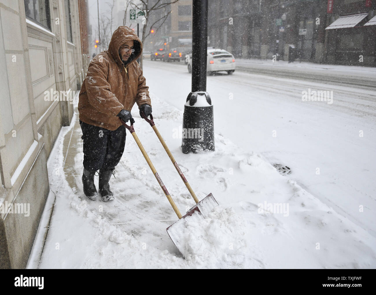 David Torres shovels snow in front of a building as a major snow storm hits on February 1, 2011 in Chicago. Up to two feet of snow is expected to fall in the Chicago area as a winter storm created blizzard conditions from the southern Great Plains to the upper midwest on Tuesday.     UPI/Brian Kersey - Stock Image