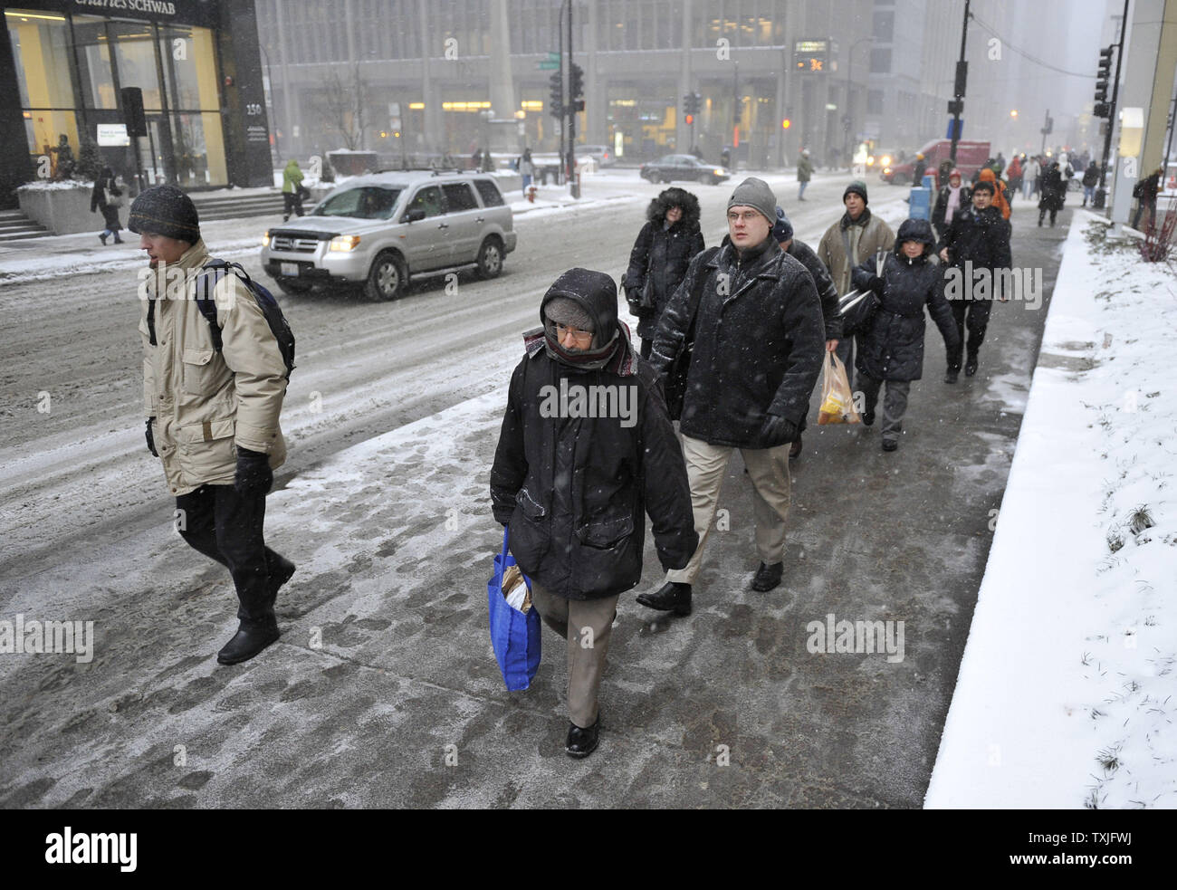 Pedestrians walk through the streets as a major snow storm hits on February 1, 2011 in Chicago. Up to two feet of snow is expected to fall in the Chicago area as a winter storm created blizzard conditions from the southern Great Plains to the upper midwest on Tuesday.     UPI/Brian Kersey - Stock Image