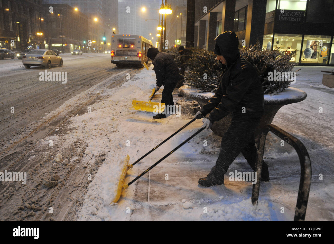 Workers shovel sidewalks as a major snow storm hits on February 1, 2011 in Chicago. Up to two feet of snow is expected to fall in the Chicago area as a winter storm created blizzard conditions from the southern Great Plains to the upper midwest on Tuesday.     UPI/Brian Kersey - Stock Image