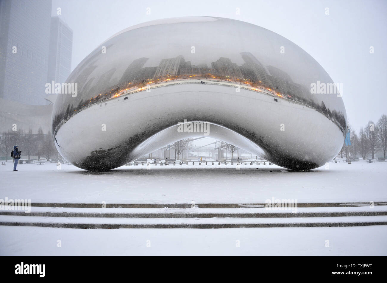 A person looks at the Cloud Gate sculpture in Millennium Park as a major snow storm hits on February 1, 2011 in Chicago. Up to two feet of snow is expected to fall in the Chicago area as a winter storm created blizzard conditions from the southern Great Plains to the upper midwest on Tuesday.     UPI/Brian Kersey - Stock Image