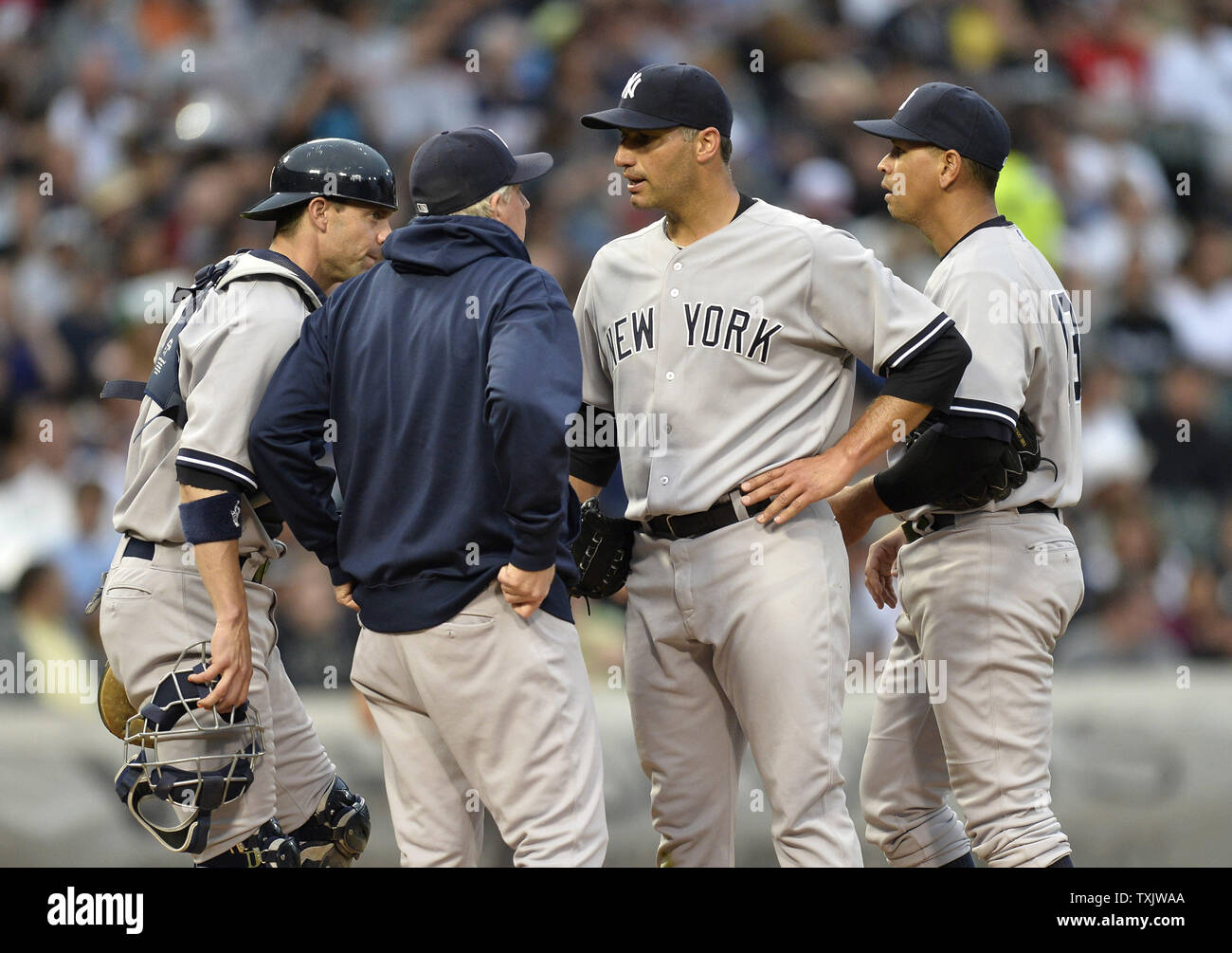 New York Yankees catcher Chris Stewart (L), pitching coach Larry Rothschild and third baseman Alex Rodriguez (R) talk with starting pitcher Andy Pettitte (C) during the second inning against the Chicago White Sox at U.S. Cellular Field in Chicago on August 5, 2013.     UPI/Brian Kersey - Stock Image