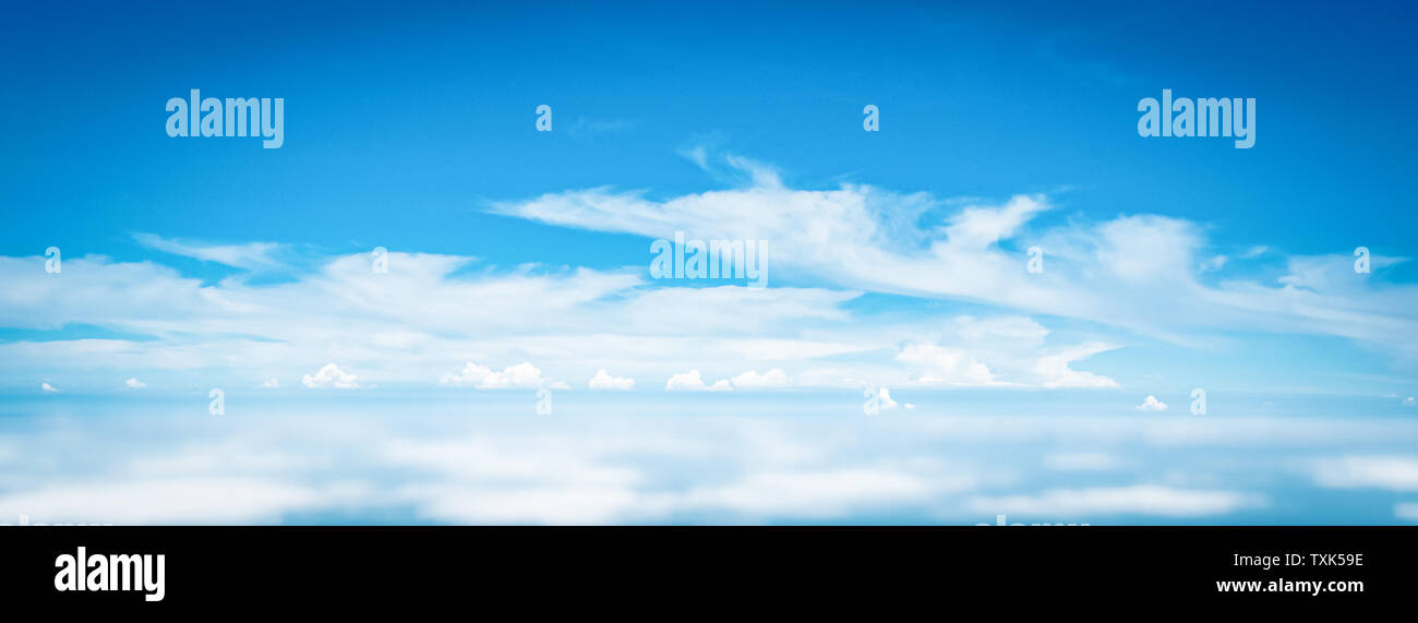 Wide Panorama sky clouds above the clouds from airplane window for banner nature background - Stock Image