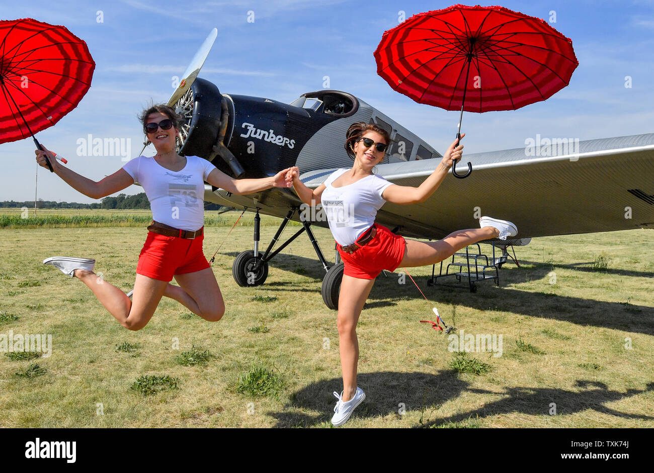 25 June 2019, Saxony-Anhalt, Dessau-Roßlau: The hostesses Pauline (l) and Vlada jump in front of a Junkers F 13 at the airfield in Dessau. Exactly 100 years ago, an aircraft of this type took off for the first time in Dessau. The aircraft, designed by aircraft pioneer Hugo Junkers, was the world's first all-metal commercial aircraft and is regarded as a pioneer in civil aviation. Since 2016, the machine has again been manufactured in small series in Switzerland. Photo: Hendrik Schmidt/dpa-Zentralbild/dpa - Stock Image