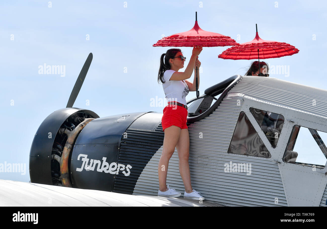 25 June 2019, Saxony-Anhalt, Dessau-Roßlau: The pilots in the cockpit of a Junkers F 13 at the airfield in Dessau are protected from the sun by hostesses with an umbrella. Exactly 100 years ago, an aircraft of this type took off for the first time in Dessau. The aircraft, designed by aircraft pioneer Hugo Junkers, was the world's first all-metal commercial aircraft and is regarded as a pioneer in civil aviation. Since 2016, the machine has again been manufactured in small series in Switzerland. Photo: Hendrik Schmidt/dpa-Zentralbild/dpa - Stock Image