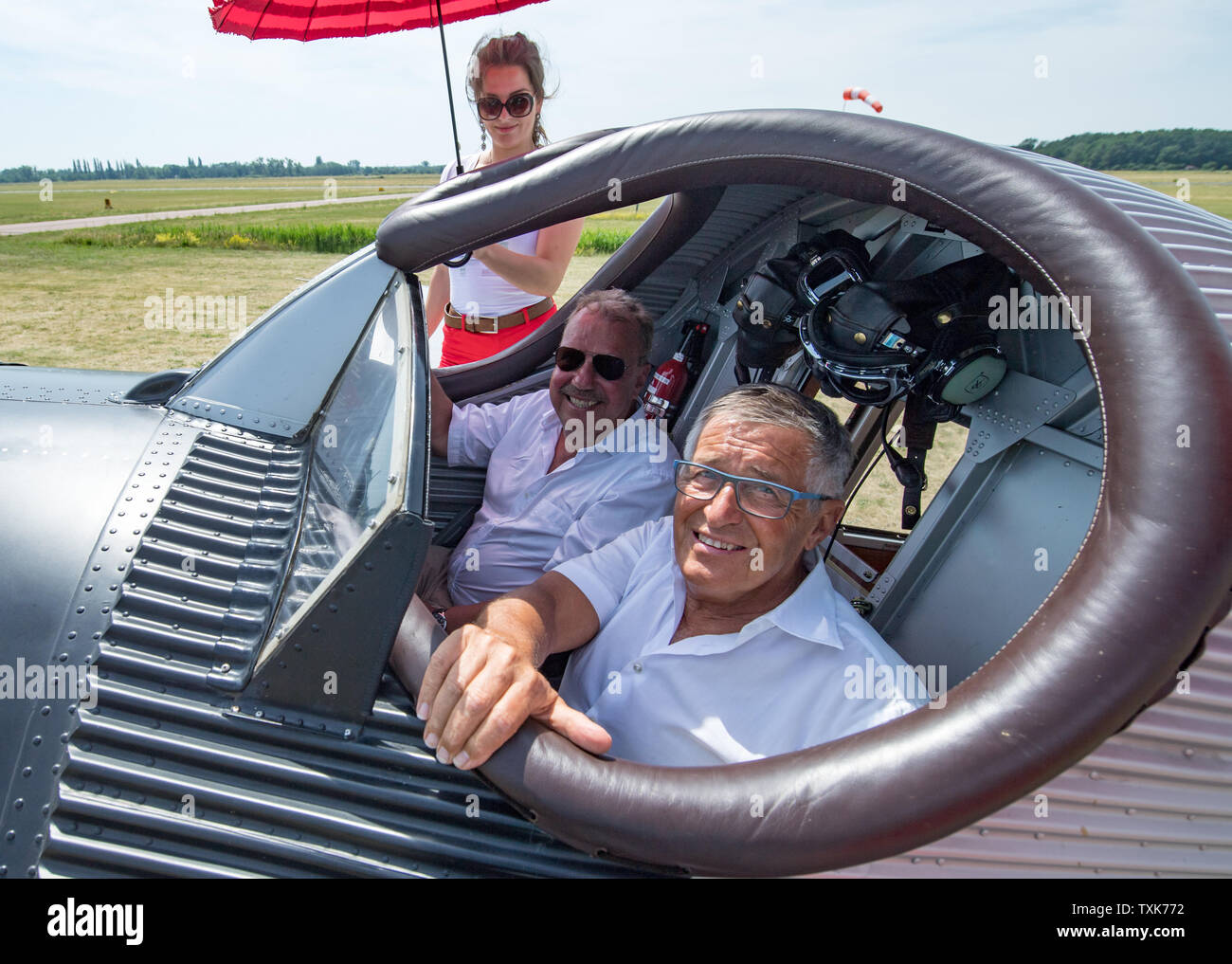 25 June 2019, Saxony-Anhalt, Dessau-Roßlau: The Cologne entrepreneur Dieter Morszeck (l.) and Kurt Waldmeier, founder of Ju-Air, sit on the airfield in Dessau as pilots in the cockpit of a Junkers F 13. Exactly 100 years ago, an aircraft of this type had taken off for the first time in Dessau. The aircraft, designed by aircraft pioneer Hugo Junkers, was the world's first all-metal commercial aircraft and is regarded as a pioneer in civil aviation. Since 2016, the machine has again been manufactured in small series in Switzerland. Photo: Hendrik Schmidt/dpa-Zentralbild/dpa - Stock Image