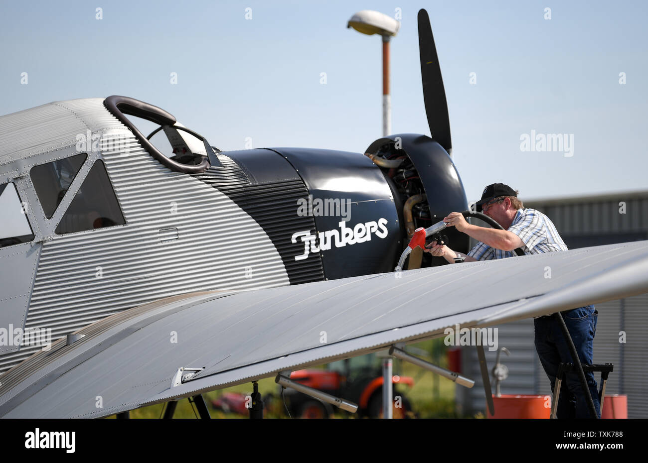 25 June 2019, Saxony-Anhalt, Dessau-Roßlau: A Junkers F 13 aircraft is refuelled at the airfield in Dessau. Exactly 100 years ago, an aircraft of this type took off for the first time in Dessau. The aircraft, designed by aircraft pioneer Hugo Junkers, was the world's first all-metal commercial aircraft and is regarded as a pioneer in civil aviation. Since 2016, the machine has again been manufactured in small series in Switzerland. Photo: Hendrik Schmidt/dpa-Zentralbild/dpa - Stock Image