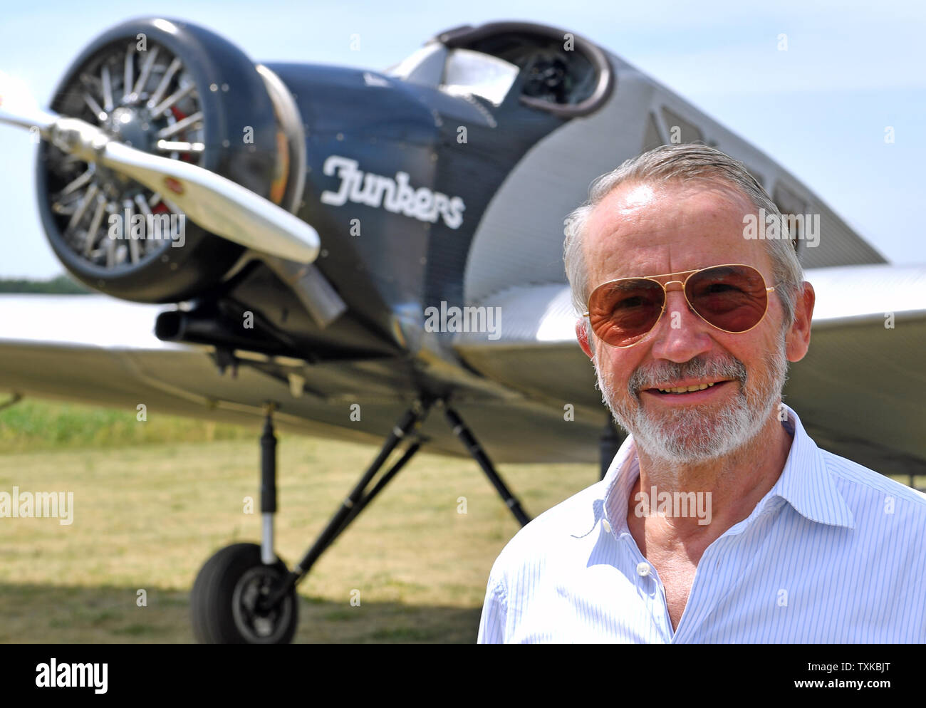 25 June 2019, Saxony-Anhalt, Dessau-Roßlau: Bernd Junkers, grandson of the aircraft pioneer Hugo Junkers, is standing at the airfield in Dessau in front of a Junkers F 13. Exactly 100 years ago, an aircraft of this type had taken off for the first time in Dessau. The aircraft, designed by aircraft pioneer Hugo Junkers, was the world's first all-metal commercial aircraft and is regarded as a pioneer in civil aviation. Since 2016, the machine has again been manufactured in small series in Switzerland. The 100th anniversary of the first flight will be celebrated in Dessau with an airport festival - Stock Image