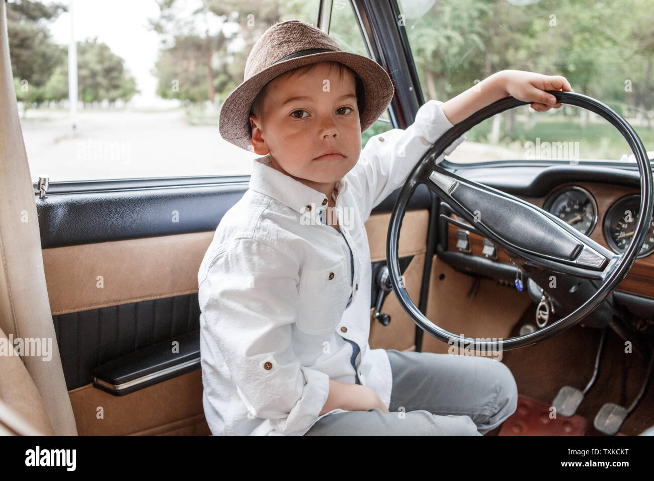 Caucasian little boy in vintage clothes sitting inside a retro car Stock Photo