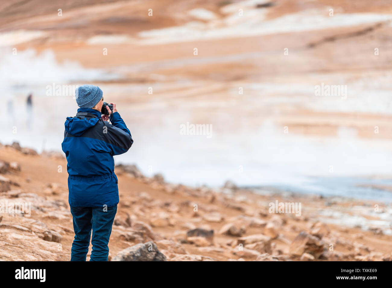 Hverir, Iceland - June 16, 2018: Hot fumaroles with people tourist one woman in coat looking at view with geyser in geothermal spot area by Myvatn lak - Stock Image