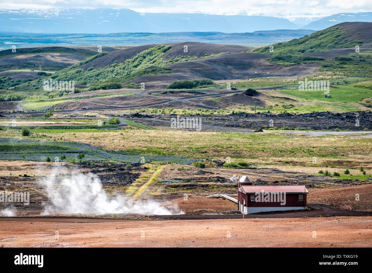 Reykjahlid, Iceland landscape high angle view near lake Myvatn and fumaroles steam vents during cloudy day by house - Stock Image