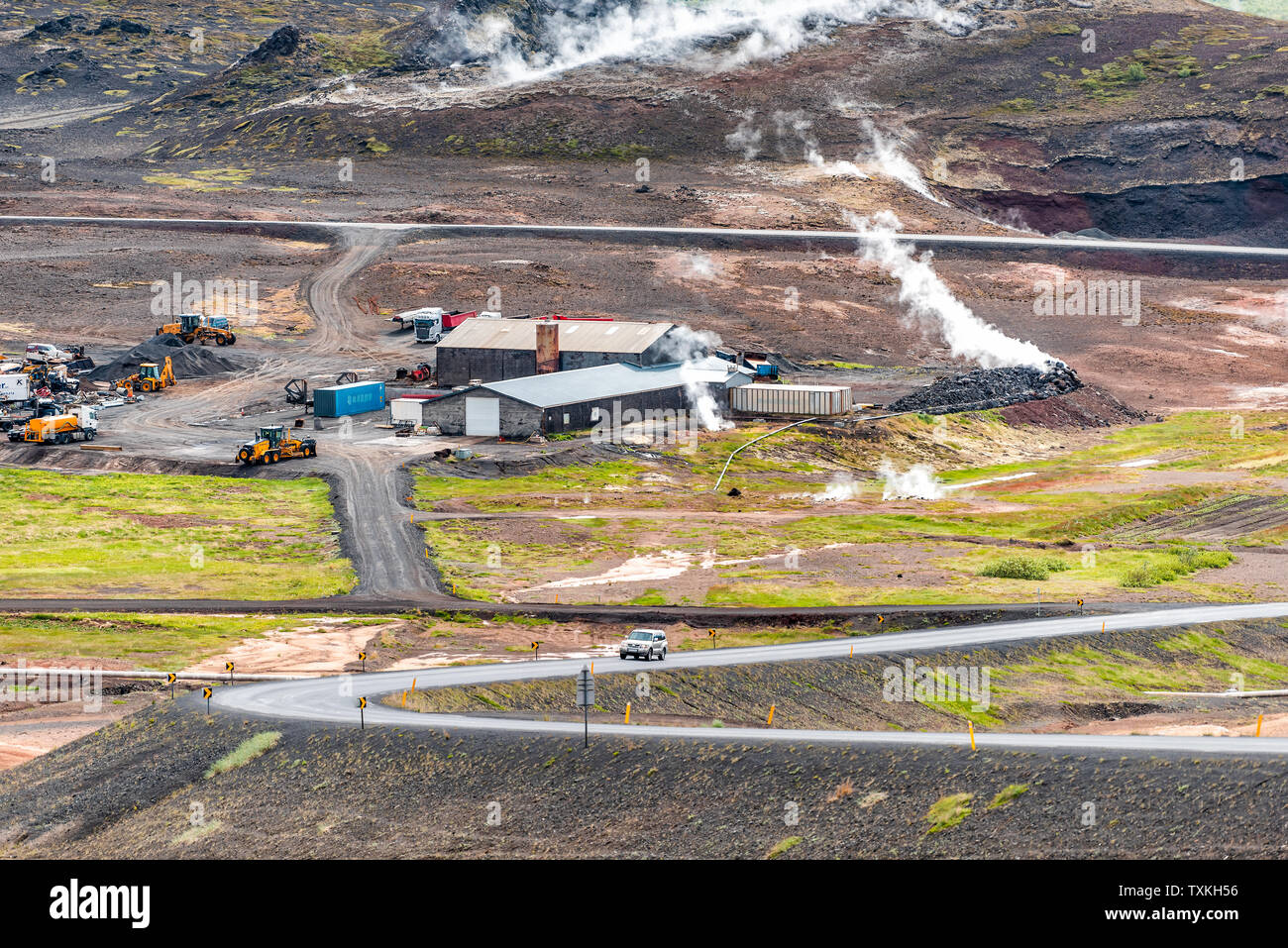 Reykjahlid, Iceland - June 16, 2018: Landscape high angle view near lake Myvatn and steam vents during cloudy day by house and ring road - Stock Image