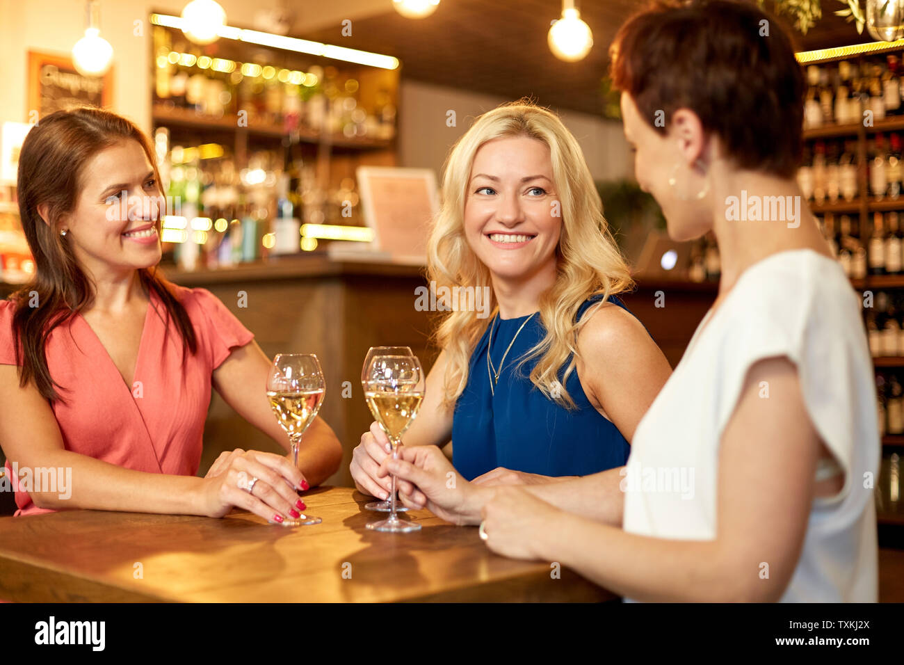 happy women drinking wine at bar or restaurant - Stock Image