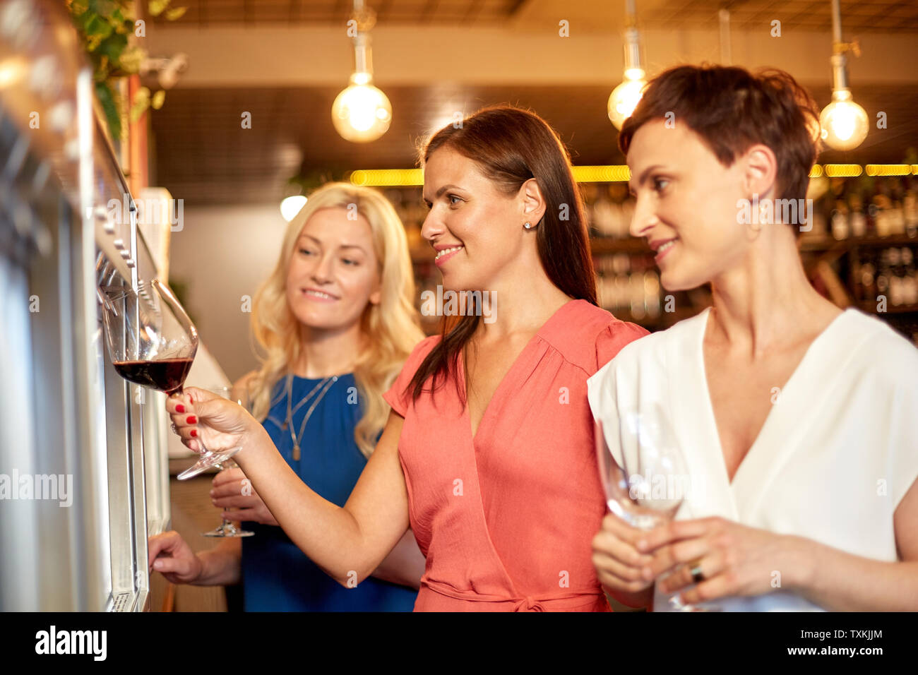 happy women pouring wine from dispenser at bar - Stock Image
