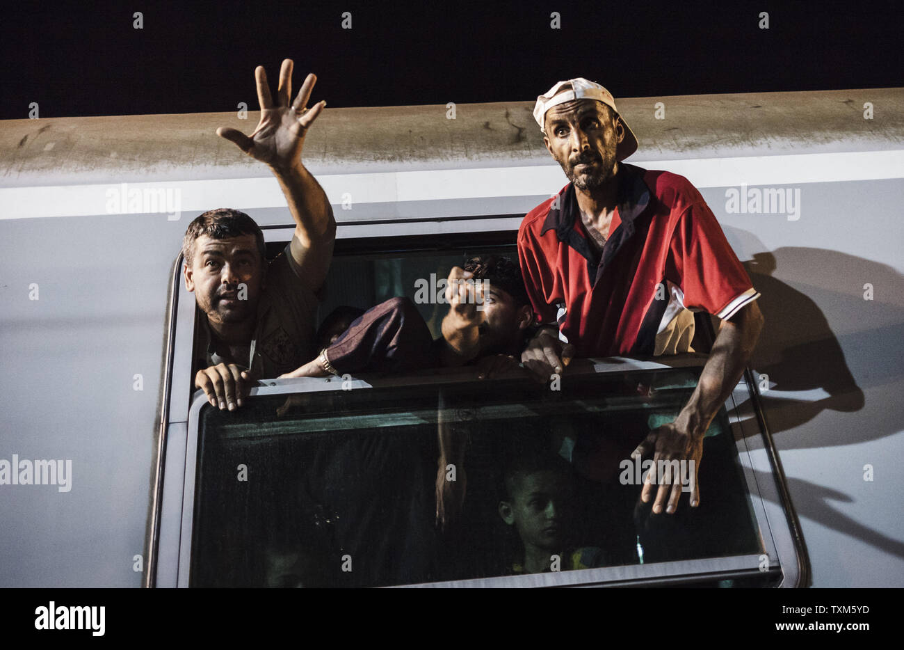 Migrants and refugees wave from a window of a train in the Tovarnik train station that will transport them to Austria on September 18, 2015 in Tovarnik, Croatia.  Photo by Achilleas Savallis/UPI. - Stock Image