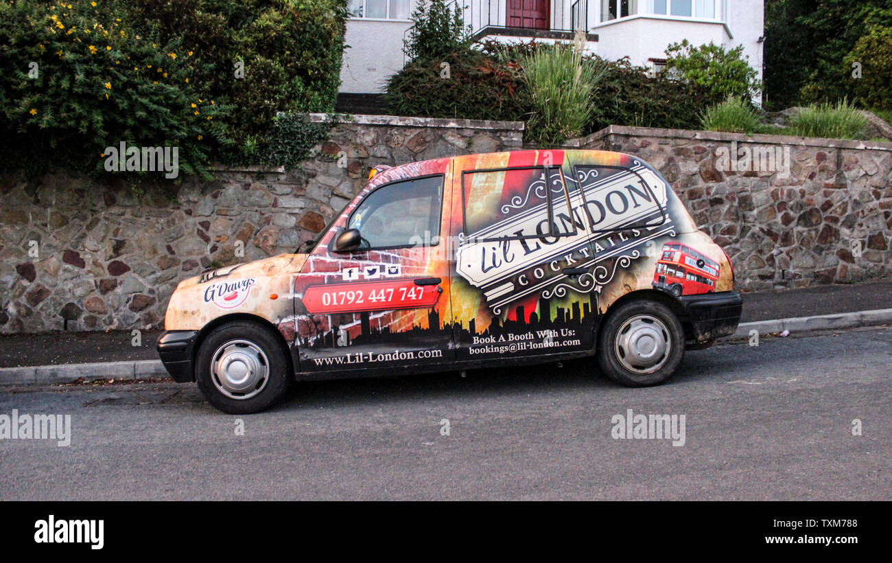 June 2019, Swansea, Wales. Lil London Cocktails Bar Advertised on a black cab.Traditional London taxi covered as a wrap with bar advertising parked in - Stock Image