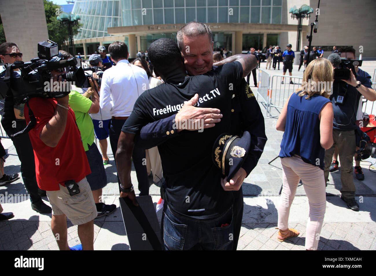 Ken Nwadike hugs an officer with the Dallas Police