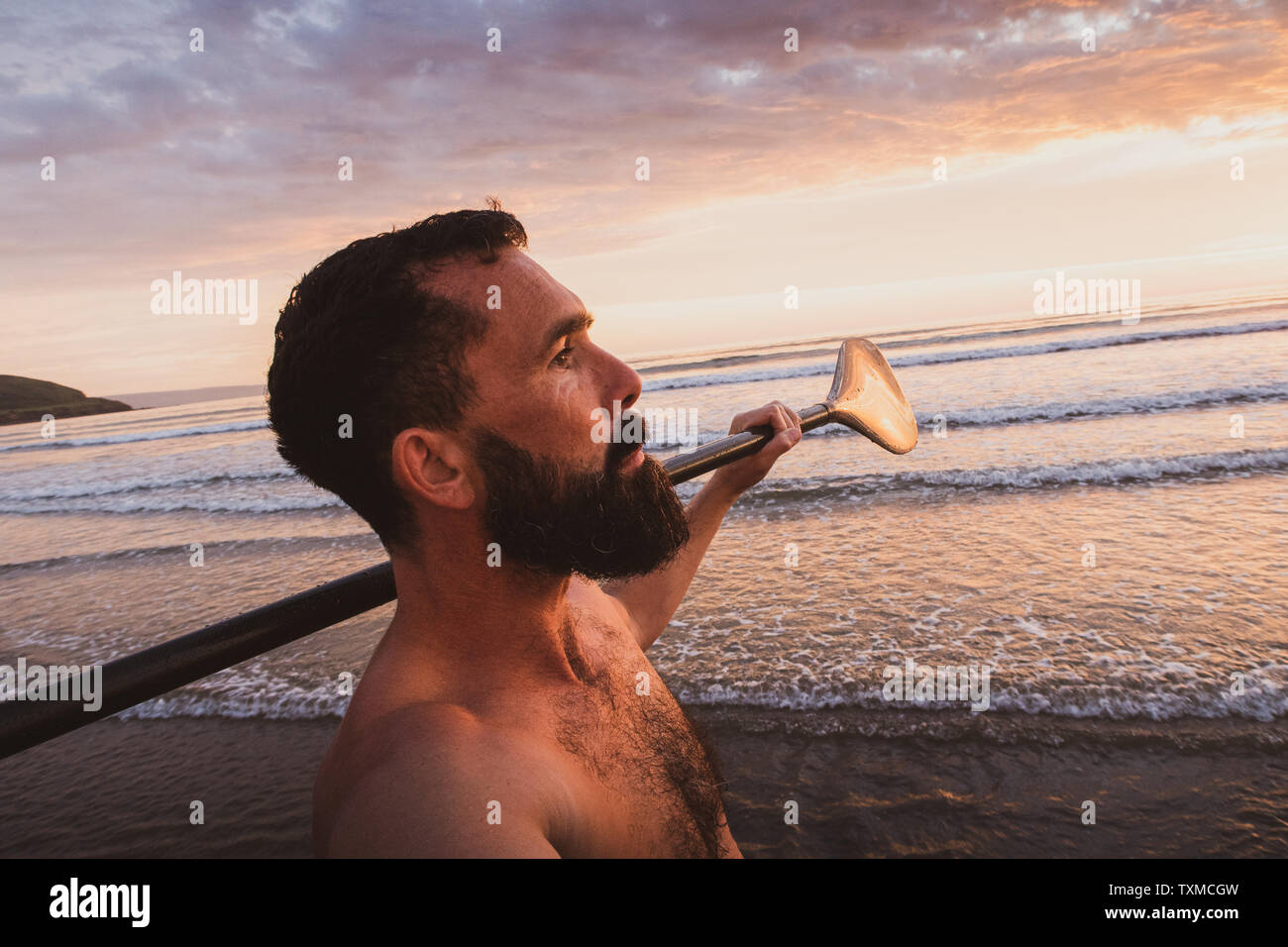 A bearded man walks towards the sea with a Stand Up Paddle board and paddle at sunset on the beach in Devon UK Stock Photo