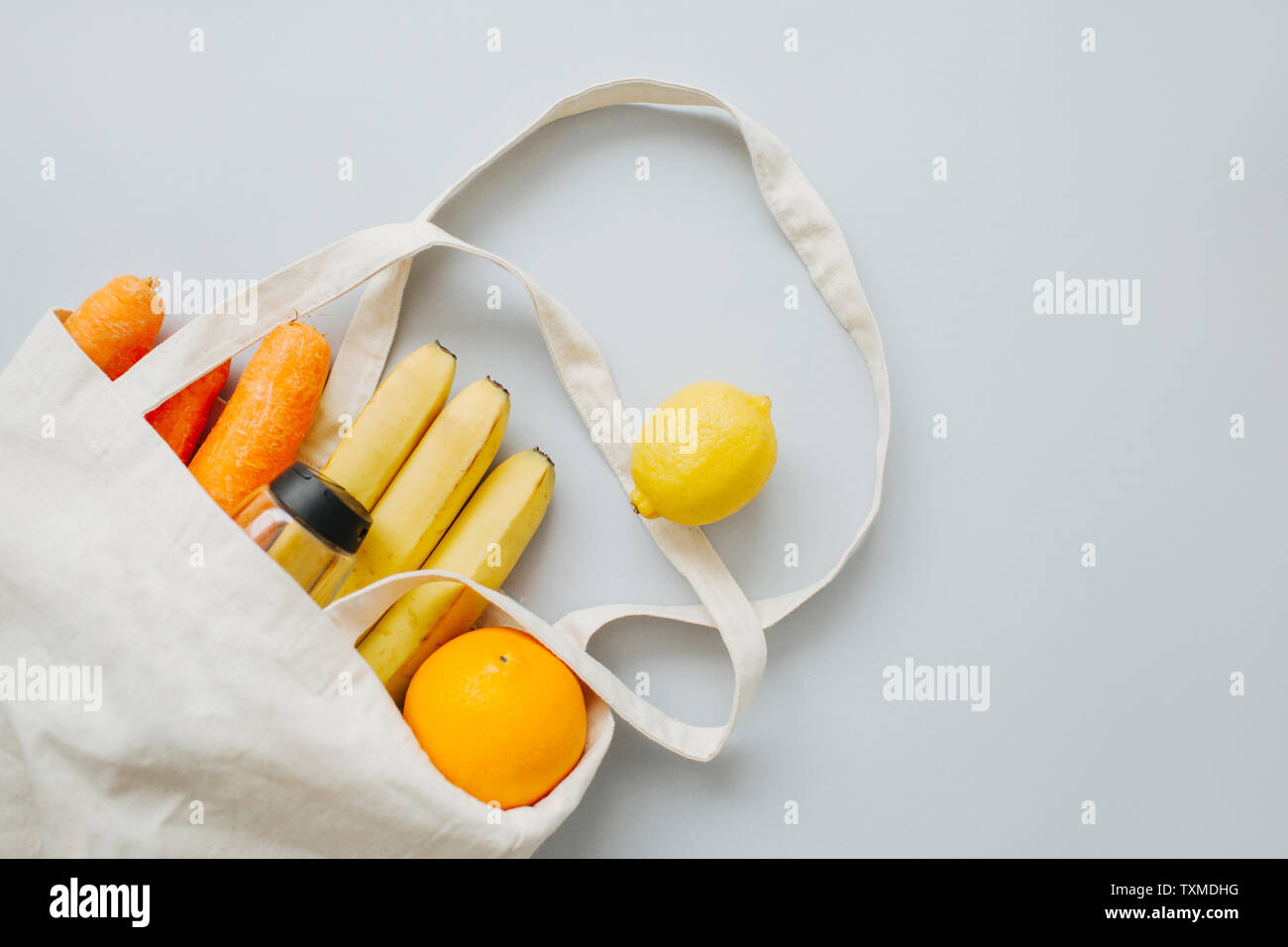 Fresh organic fruit and vegetables in a linen bag on a light grey background. Eco lifestyle, zero waste concept. No plastic living. - Stock Image
