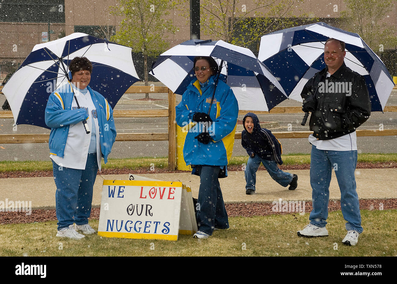 Denver Nuggets fans take cover under umbrellas as snow begins to fall before Los Angeles Lakers and Denver Nuggets Western Conference quarterfinals game three at the Pepsi Center in Denver on April 26, 2008.  Los Angeles leads the series against Denver 2-0.    (UPI Photo/Gary C. Caskey) - Stock Image