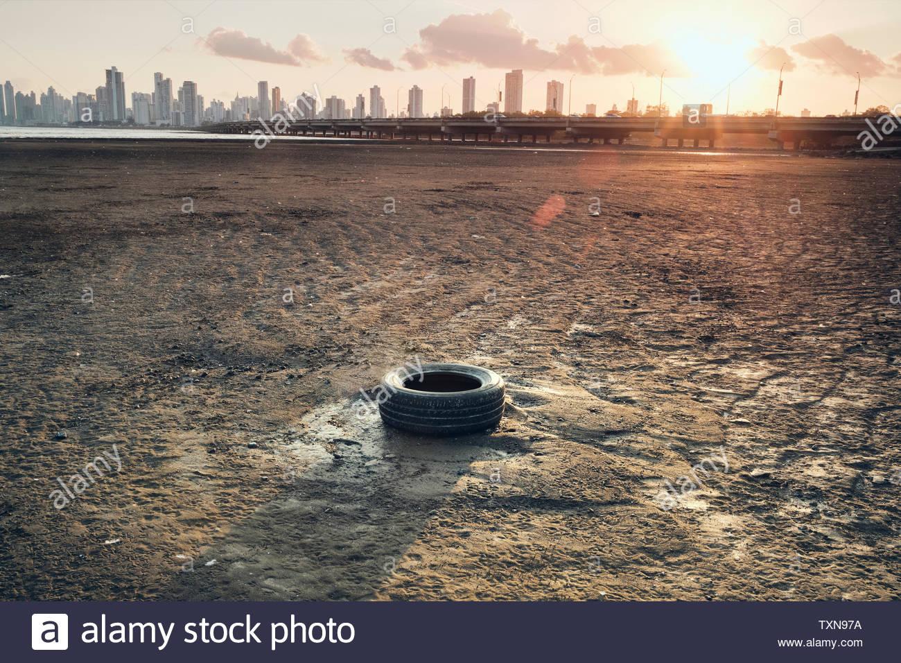 Discarded tyre on seashore, Costa del Este, Ciudad de Panamá, Panama - Stock Image