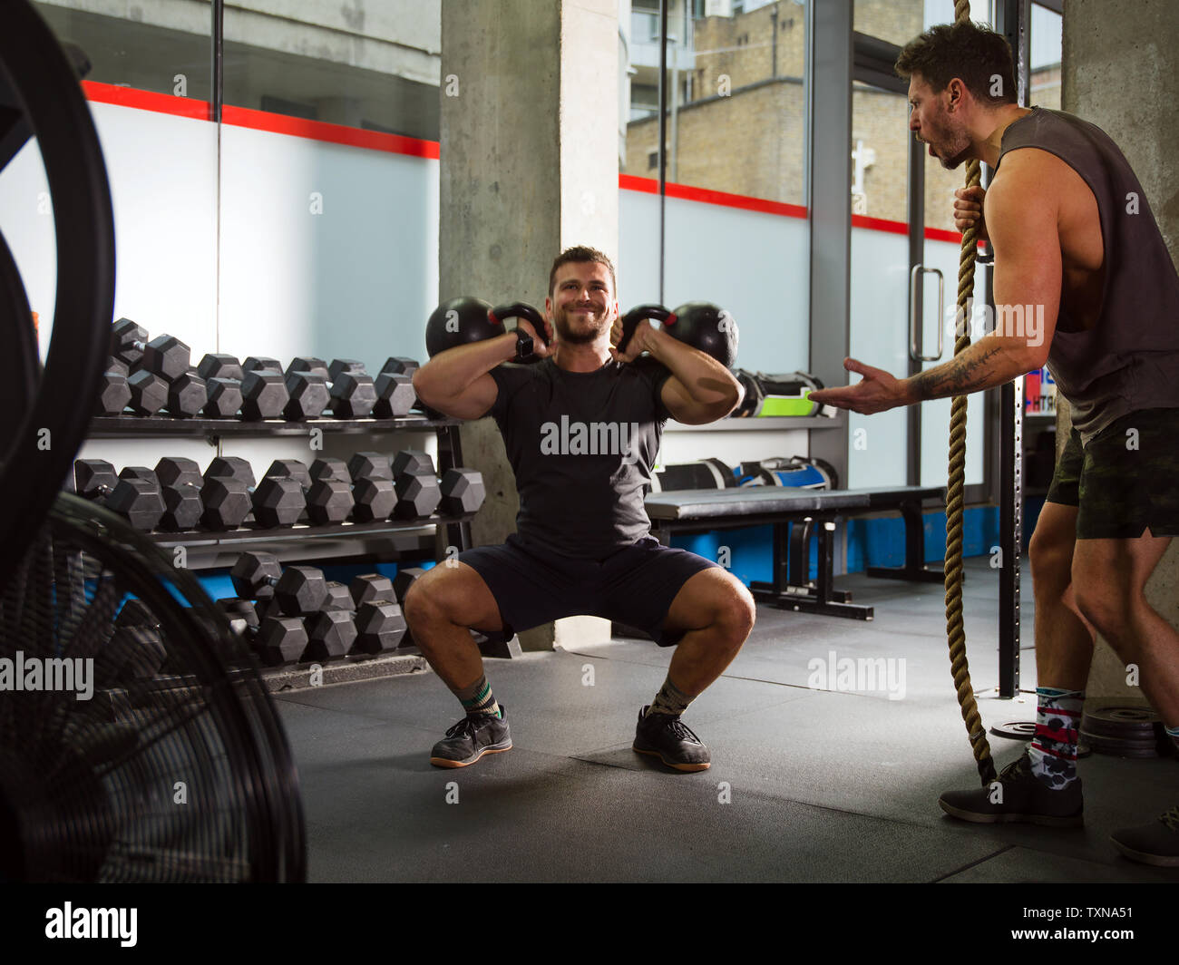 Man motivating friend doing squats, lifting kettlebells in gym - Stock Image