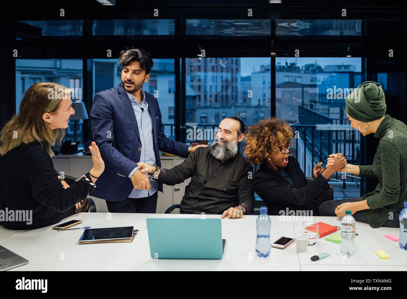 Business partners rejoicing in office Stock Photo