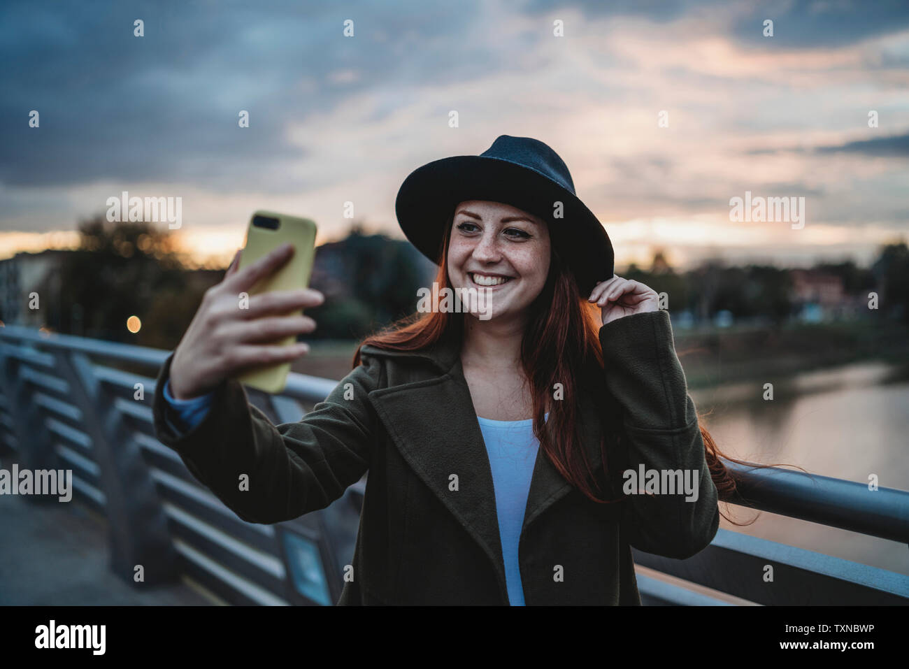 Young woman with long red hair on footbridge taking smartphone selfie at dusk, Florence, Tuscany, Italy Stock Photo
