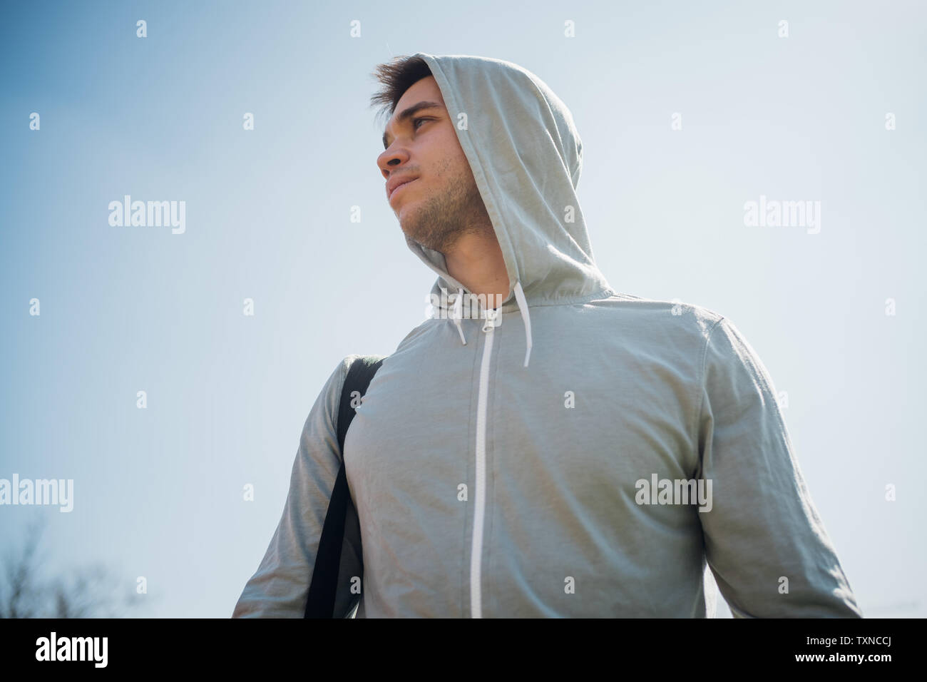 Calisthenics in park, young man in hoody against blue sky - Stock Image