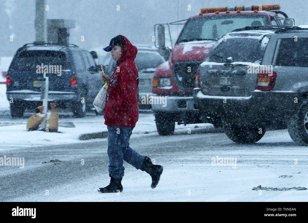 A pedestrian crosses the road as the snow begins to fall heavily during a winter storm in Denver on December 30, 2010.               UPI/Gary C. Caskey - Stock Image