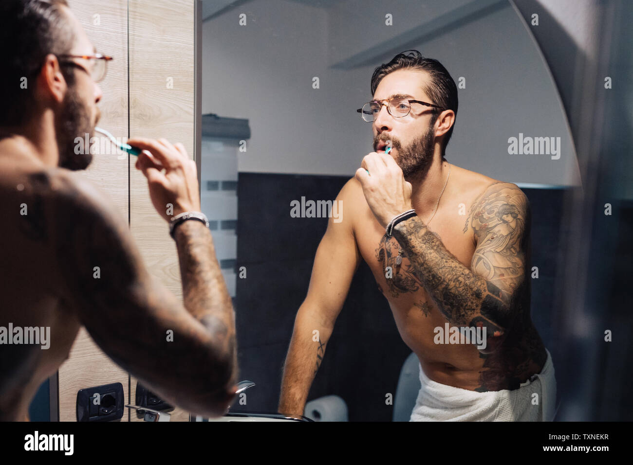 Mid adult man with tattoos brushing teeth at bathroom mirror - Stock Image