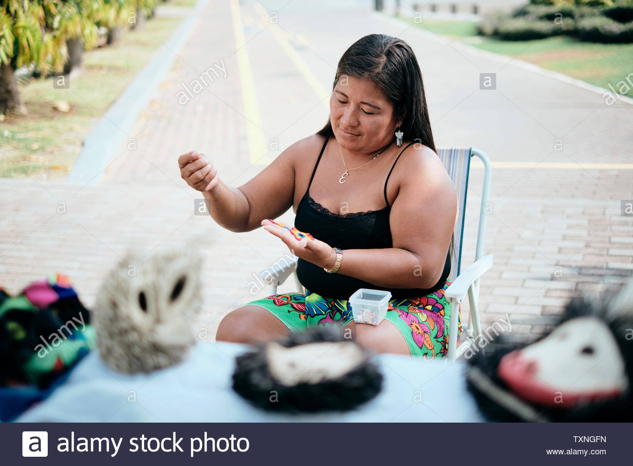 Indigenous woman beading flower coaster at stall, Ciudad de Panamá, Panama - Stock Image