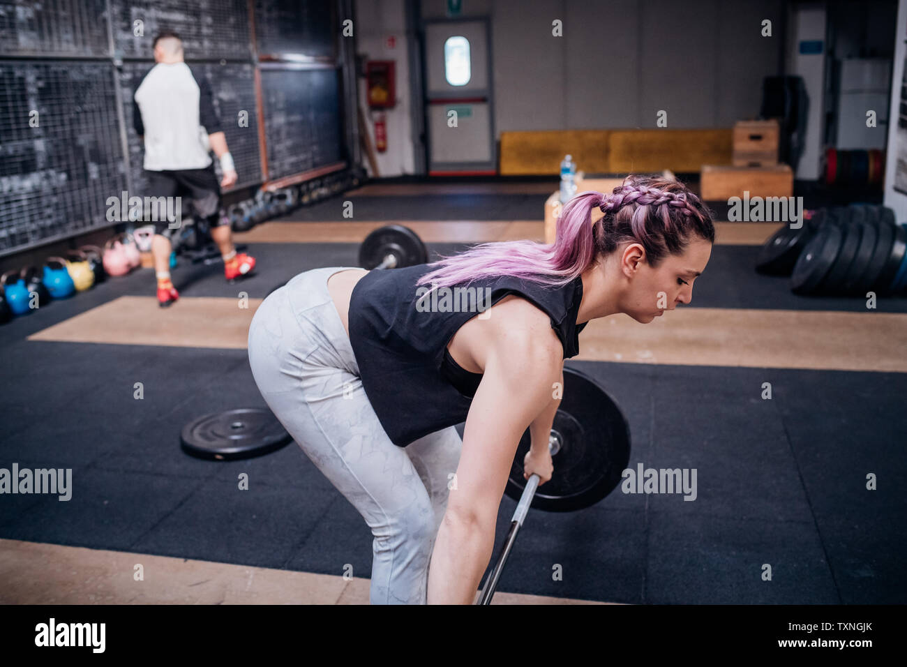 Young woman lifting barbell in gym - Stock Image