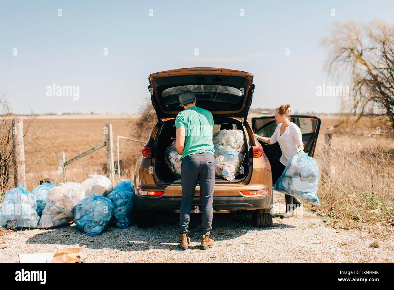 Couple putting rubbish bags into boot, Georgetown, Canada - Stock Image