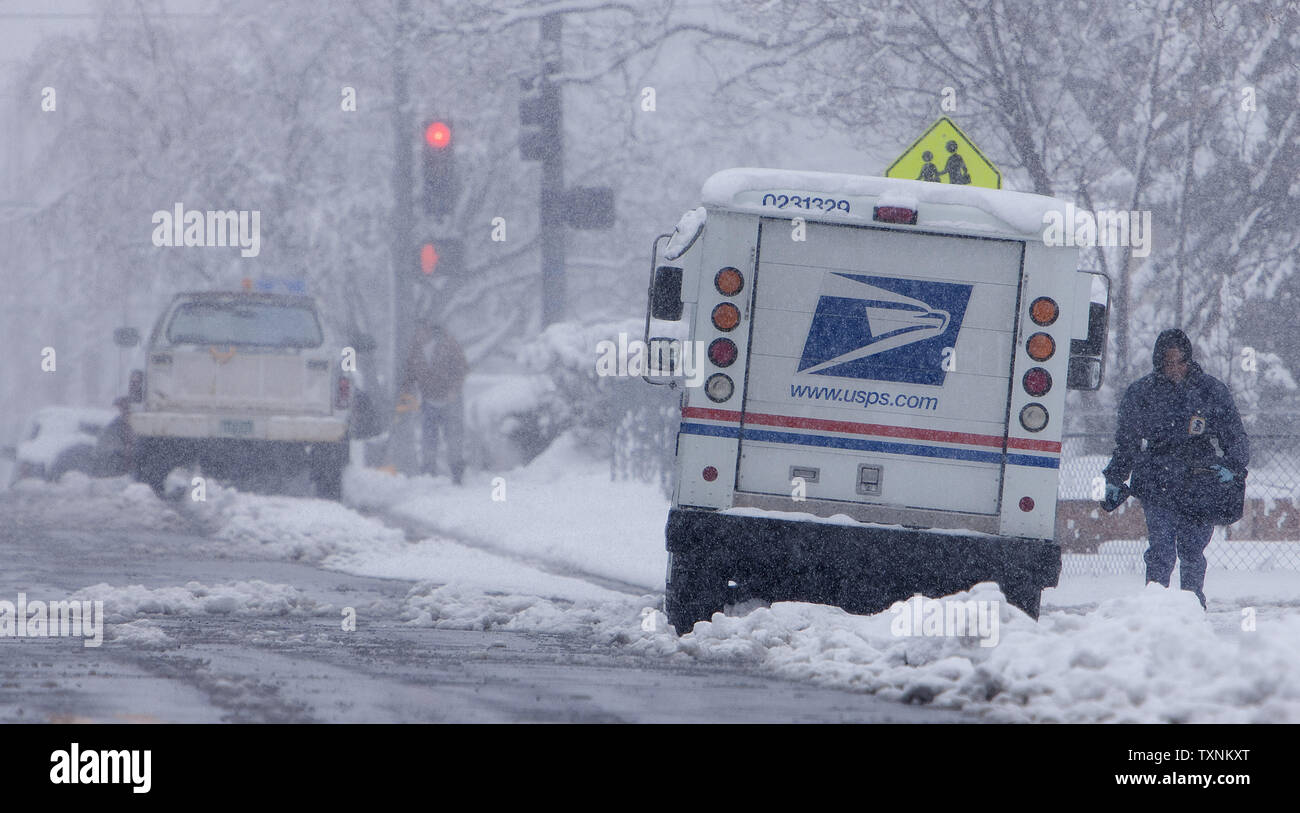 A US postal worker finds wet heavy snowfall  makes for difficult conditions delivering mail on a Saturday during a winter storm in Denver on March 9, 2013.  Weather reports indicated 6-12 inches of snow shall fall in the area before the quick moving storm moves out into the eastern plains.     UPI/Gary C. Caskey - Stock Image