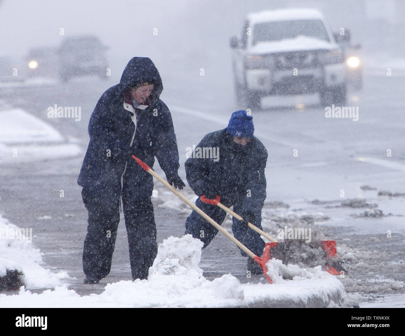 Workers clear sidewalks of heavy wet snow during a winter storm in Denver on March 9, 2013.  Weather reports indicated 6-12 inches of snow shall fall in the area before the quick moving storm moves out into the eastern plains.     UPI/Gary C. Caskey - Stock Image
