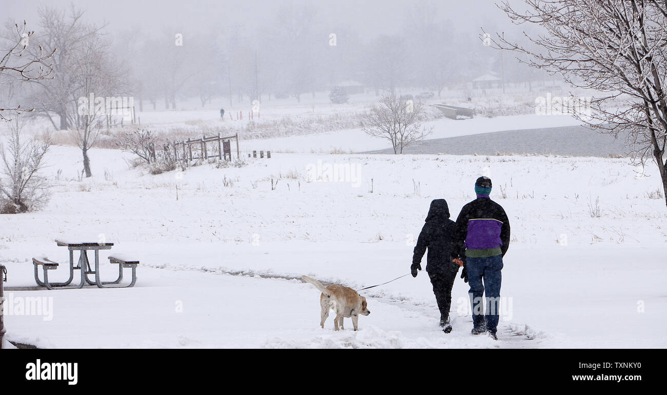 Residents take their dog for a walk in the early hours of a day long winter storm in Denver on March 9, 2013.  Weather reports indicated 6-12 inches of snow shall fall in the area before the quick moving storm moves out into the eastern plains.     UPI/Gary C. Caskey - Stock Image