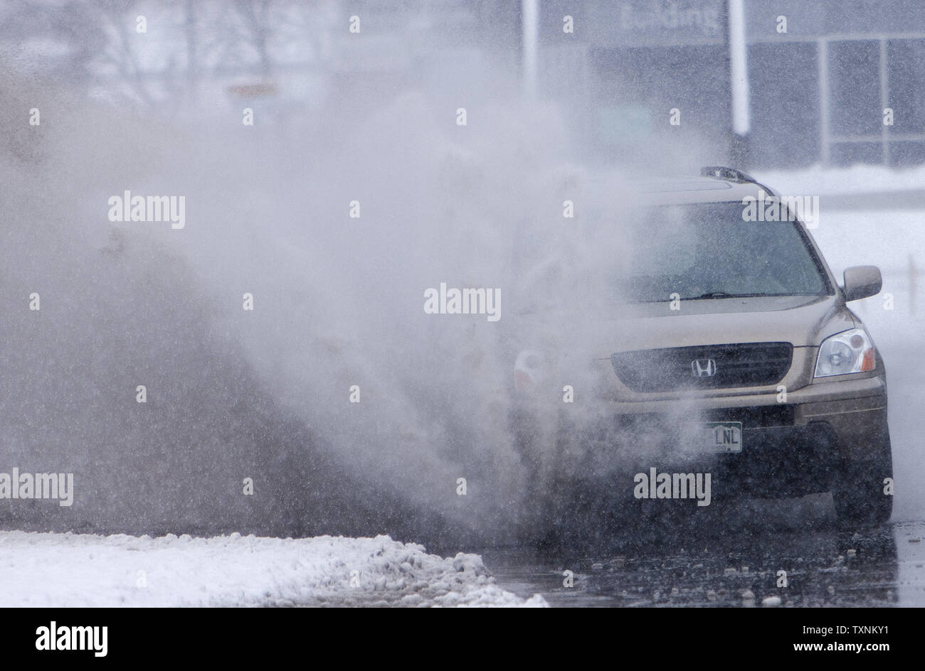 With heavy wet snow falling, slow drainage made for large puddles as cars navigate during a winter storm in Denver on March 9, 2013.  Weather reports indicated 6-12 inches of snow shall fall in the area before the quick moving storm moves out into the eastern plains.     UPI/Gary C. Caskey - Stock Image