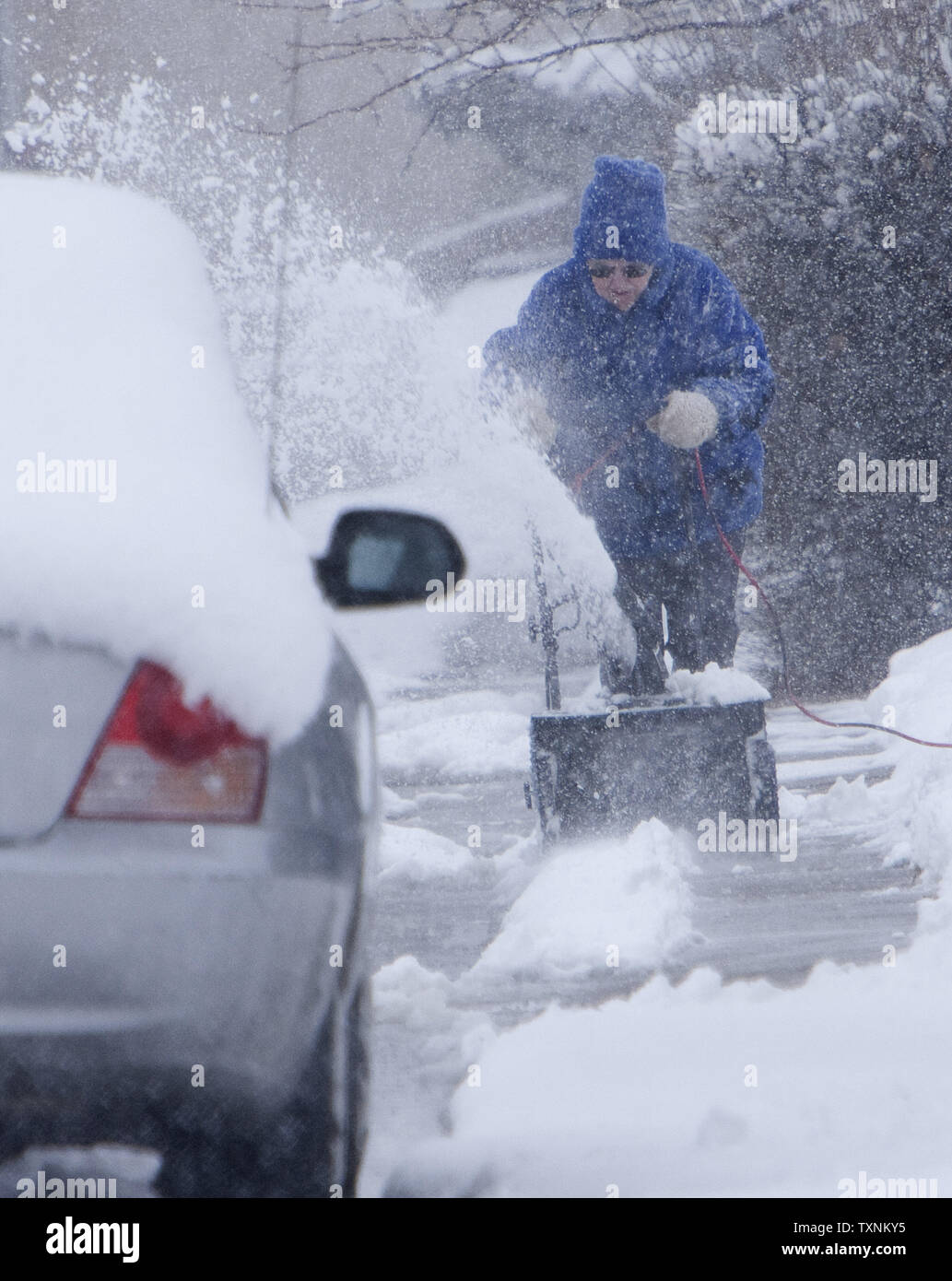 A resident clears her sidewalk during a winter storm in Denver on March 9, 2013.  Weather reports indicated 6-12 inches of snow shall fall in the area before the quick moving storm moves out into the eastern plains.     UPI/Gary C. Caskey - Stock Image