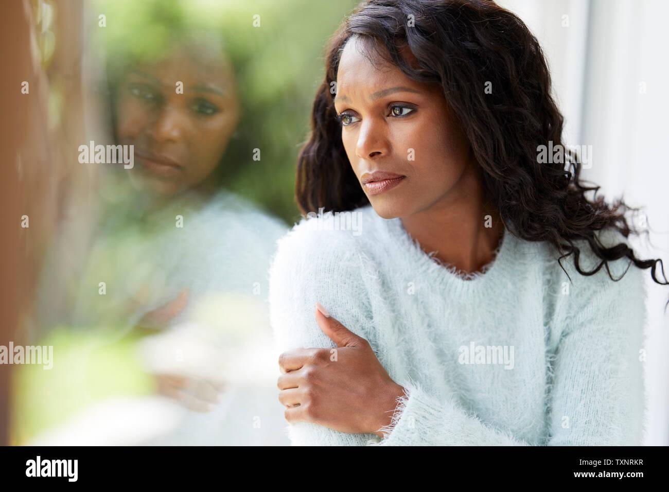 Ethnic woman looking sad sat in a window Stock Photo