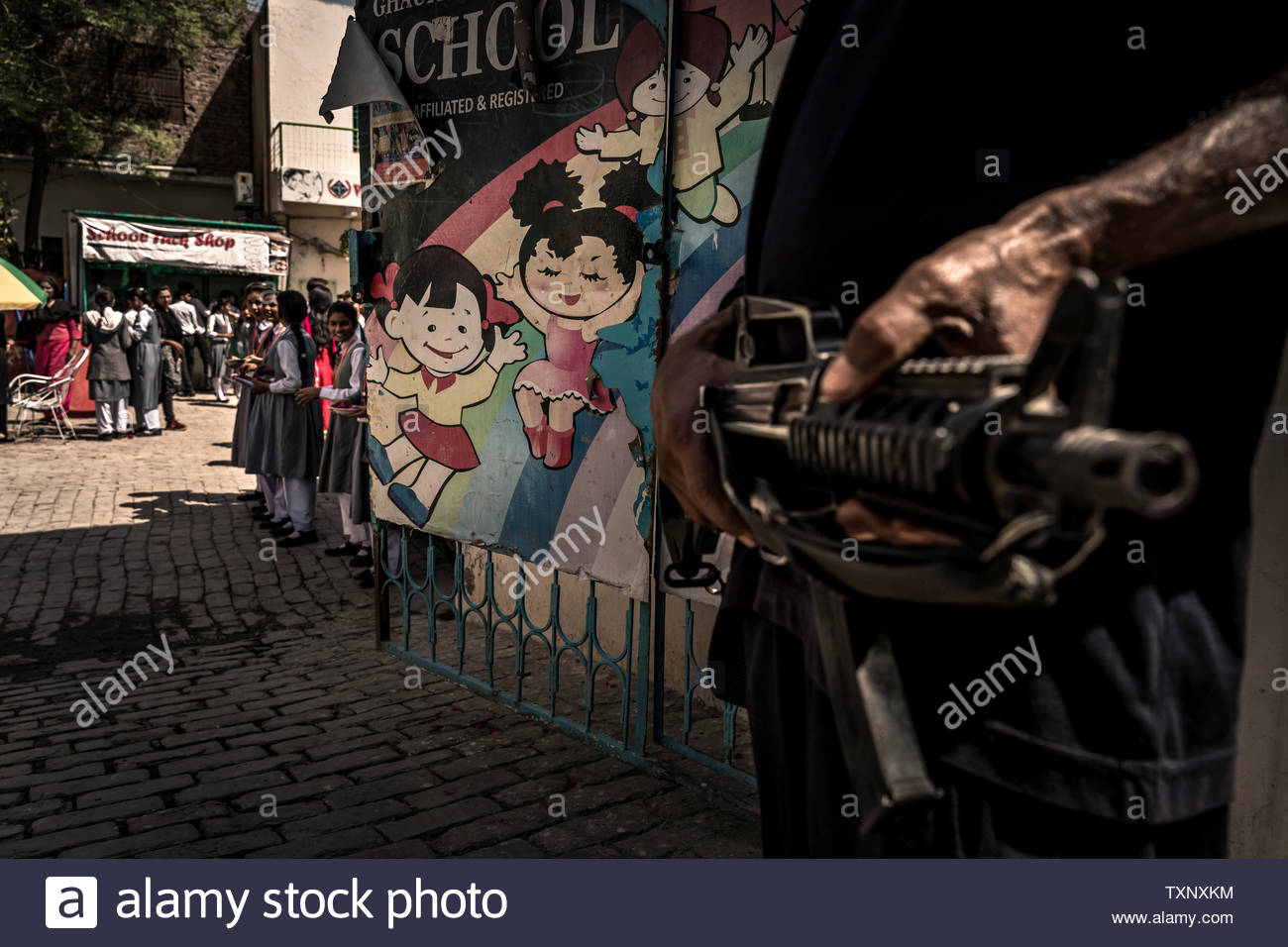 Security service with weapon in front of Christian orphanage with school in the largest Christian quarter Youhanabad, Lahore, Punjab, Pakistan. Stock Photo
