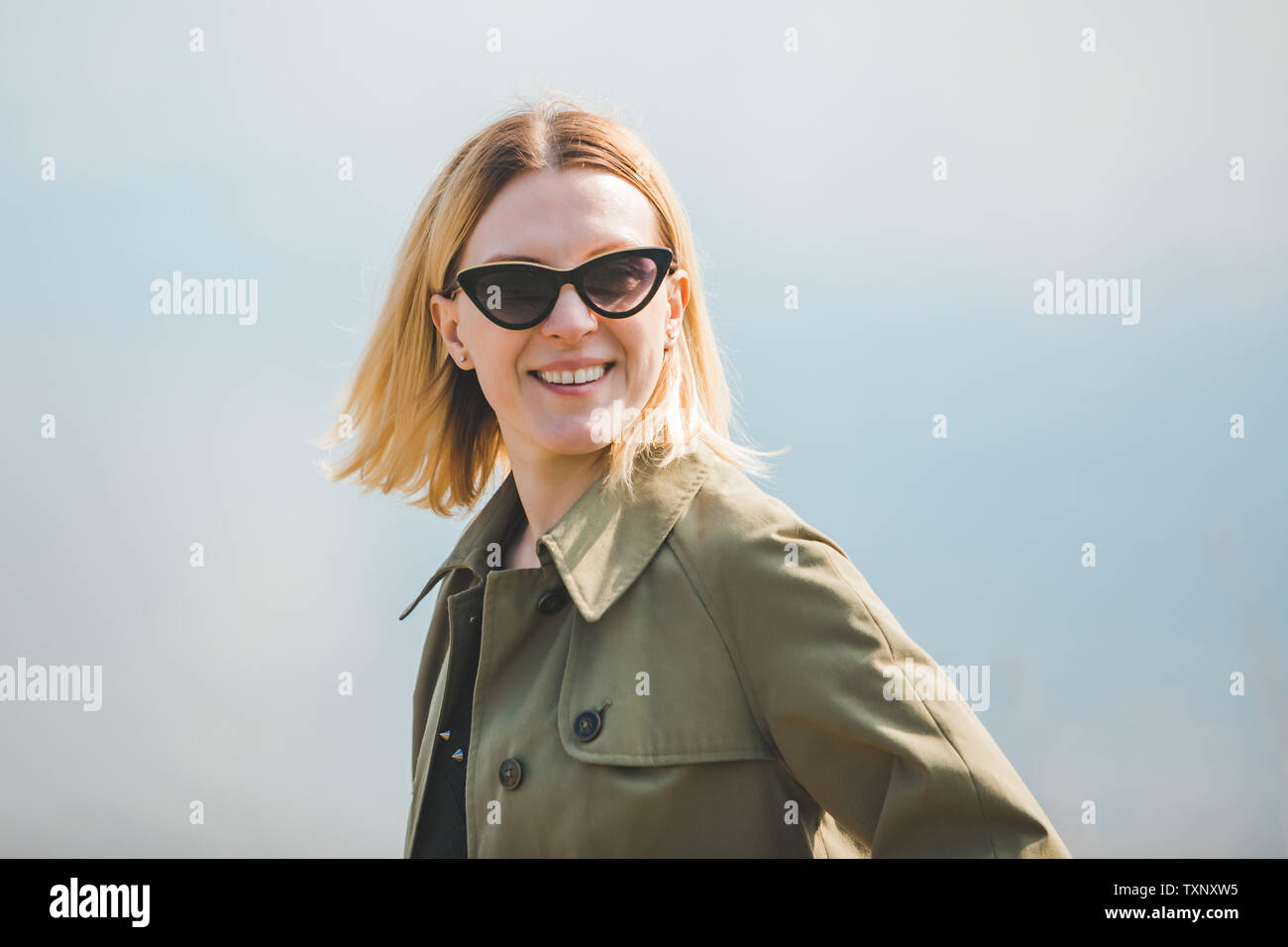 portrait of pretty smiling blond woman in sunglasses and coat. sunny day - Stock Image