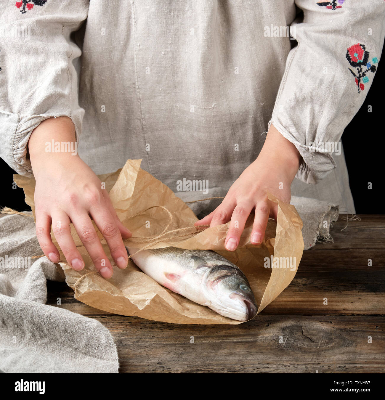 female hands are wrapped in brown paper whole fresh sea bass fish on a wooden table, black background - Stock Image